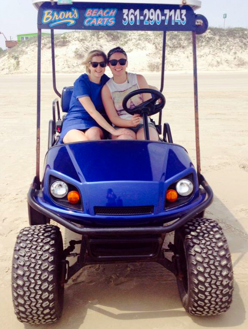 2 girls in blue cart at the beach